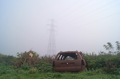 lode pylon with burnt out rusty car shell